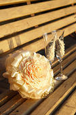 Two glasses and a wedding bouquet on wooden bench — Stock Photo