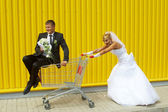 Bride and groom playing with a basket of supermarket — Stock Photo