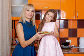 Mother with daughter standing in kitchen — Stock Photo