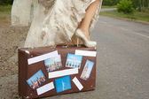 Bride with baggage on road — Stock Photo