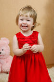 Cute laughing girl in red dress — Stock Photo