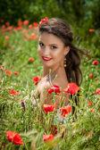 Vacker kvinna sitter i vallmo blomma — Stockfoto