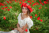 Beautiful  woman sitting in the poppy flower — Stock Photo