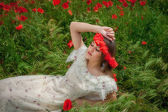 Beautiful  woman sitting in the poppy flower — ストック写真