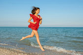 Young woman runs in red dress on the sea — Stockfoto