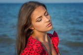 Young sad woman near the sea on a sunset — Stockfoto