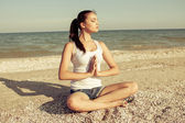 Young woman practicing yoga or fitness at seashore — Zdjęcie stockowe