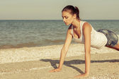 Young woman practicing yoga or fitness at seashore — Stock Photo