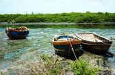 The tide ebbed away, leaving fishing boats on seaweed, marshy su — Stock Photo