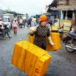Women carry plastic tray on her shoulder at fishing market. LONG HAI, VIET NAM- JULY 15 — Stock Photo