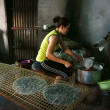Woman make girdle cake (banh trang) — Stock Photo