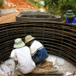 Stock Photo: Worker casting cement culvert for road-works