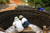Worker casting cement culvert for road-works — Stock Photo
