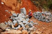 Werknemer splitsen steen voor wegwerkzaamheden — Stockfoto