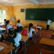 Foto Stock: Primary pupil writting on blackboard in school time