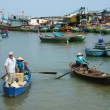 Постер, плакат: Transportation people and goods by wooden boat at habor