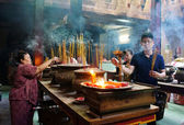 People burn incense at ancient temple — Stock Photo