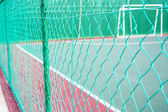 Green colored chain link fencing surrounding futsal court. — Stock Photo