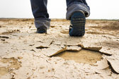 Identify man walking on dry soil — Stock Photo