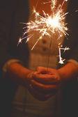 Woman holding sparkler — Stockfoto