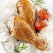Roasted chicken on a plate with tomatoes — Stock Photo