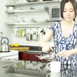 Asian girl is drinking coffee in the kitchen — Stock Video