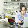 Asigirl with laptop in kitchen — Stock Video #31659403