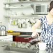Asigirl is drinking coffee in kitchen — Stock Video #31662489