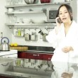 Asigirl talking on cell phone in kitchen — Stock Video #31663469