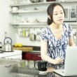Beautiful asian woman in the kitchen — Stock Video #31692675