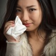Постер, плакат: Attractive asian girl cries and wipes her tears with a handkerchief