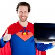 Attractive caucasian man dressed as superman holding a laptop and showing thumb up — Stock Photo