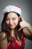 Sexy asian santa claus on grey backgroound with a call me gestur — Stock Photo