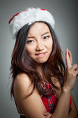 Sexy asian santa claus on grey backgroound worried with fingers — Stock Photo
