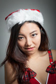 Sexy asian santa claus on grey backgroound biting lips — Stock Photo