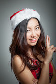 Sexy asian santa claus on grey backgroound smiling with fingers — Stock Photo