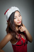Sexy asian santa claus on grey backgroound pointing — Stock Photo