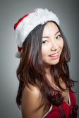 Sexy asian santa claus on grey backgroound smiling — Stock Photo