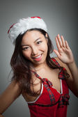 Sexy asian santa claus on grey backgroound smiling and waving — Stock Photo