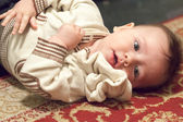Kid lying on carpet — Stock Photo