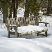Wooden bench in snow — Stock Photo