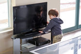Boy try to switch on the tv — 图库照片