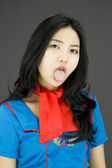 Stewardess poking out tongue — Stock Photo