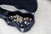 Coins in a guitar case — Stock Photo