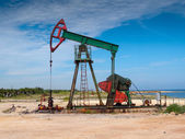 Oil well pump on the beach — Stock Photo