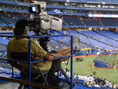 Cameraman filming a baseball match — Stock Photo