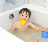 Pojke spelar i ett badkar — Stockfoto