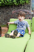 Boy sitting on a lounge chair — Stock fotografie