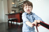 Boy pulling a bag and sulking — Stock Photo