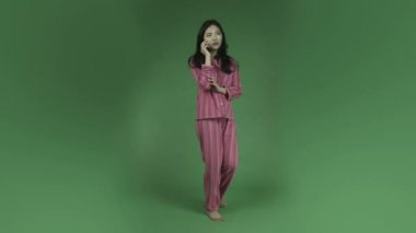 Woman in pajamas talking on cell phone — Stock Video